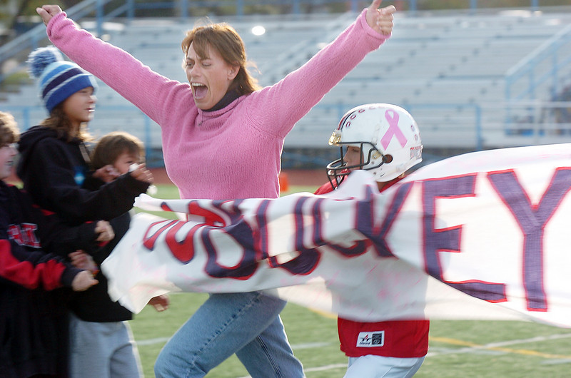 Michelle Lucero, a breast cancer patient, runs through the Buckeye banner with her son Ryan to start the game dedicated to her by the Buckeyes a Broomfield Youth Football team playoff game on Saturday at Elizabeth Kennedy Stadium. The team wore pink items to help raise awareness to fight breast cancer.<br /> October 9, 2010<br /> staff photo/David R. Jennings