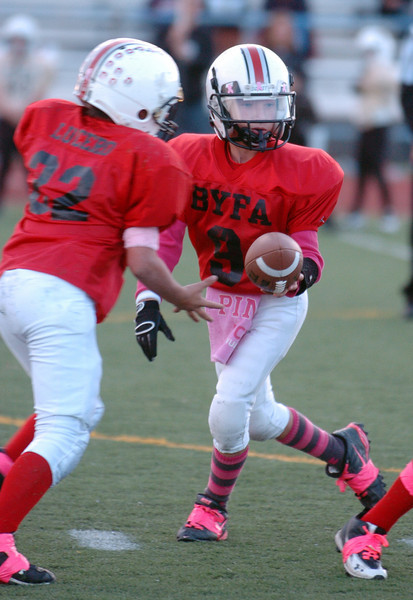 Broomfield Youth Football Buckeyes quarterback Mitchell Gorman, right, hands off to Ryan Lucero during the playoff game dedicated to Lucero's mother Michelle, a breast cancer patient, on Saturday at Elizabeth Kennedy Stadium. The Buckeyes wore pink items on their uniforms in honor of Michelle Lucero and to help show awareness to fighting breast cancer.<br /> October 9, 2010<br /> staff photo/David R. Jennings