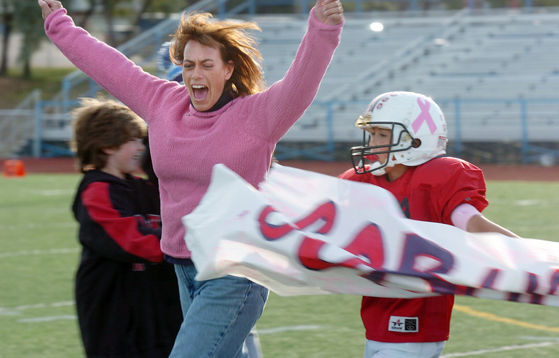 Michelle Lucero, a breast cancer patient, runs through the Buckeye banner with her son Ryan to start the playoff game dedicated to her by the Buckeyes a Broomfield Youth Football team on Saturday at Elizabeth Kennedy Stadium. The team wore pink items to help raise awareness to fight breast cancer.<br /> October 9, 2010<br /> staff photo/David R. Jennings