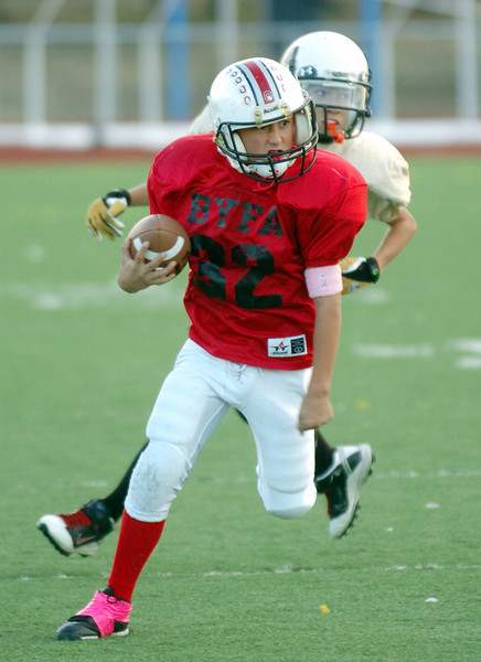 Ryan Lucero, Broomfield Youth Football team the Buckeyes, runs the ball downfield for a touchdown during the playoff game dedicated to Lucero's mother, Michelle, a breast cancer patient, on Saturday at Elizabeth Kennedy Stadium.<br /> October 9, 2010<br /> staff photo/David R. Jennings
