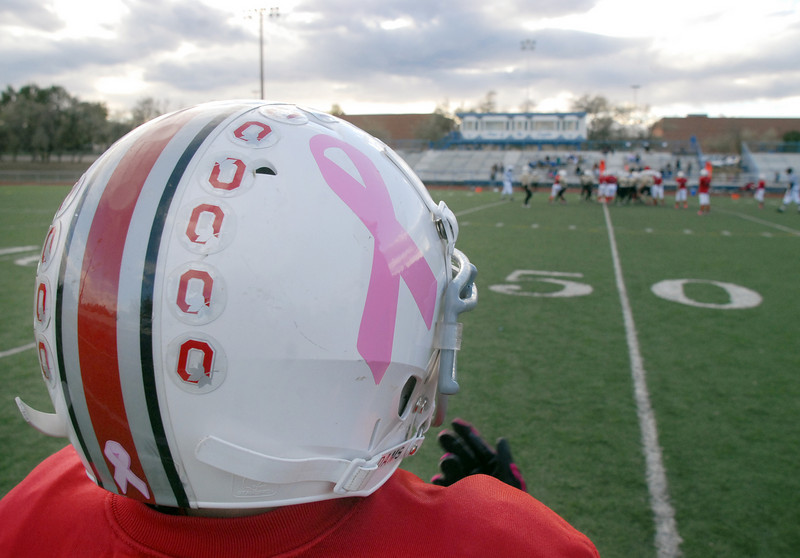The Broomfield Youth Football team the Buckeyes wore pink ribbon stickers on their helmets as well as pink sweat bands and pink tape on their shoes in honor of parent Michelle Lucero, a breast cancer patient, for their playoff game on Saturday at Elizabeth Kennedy Stadium.<br /> October 9, 2010<br /> staff photo/David R. Jennings