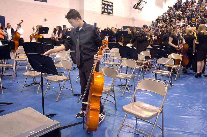 Cellist Derek Do, 14, Northglenn High, picks up his music after the Adams 12 Five Stars Schools Orchestra Festival at Legacy High School on Saturday.<br /> For more photos please see broomfieldenterprise.com.<br /> December 3, 2011<br /> staff photo/ David R. Jennings