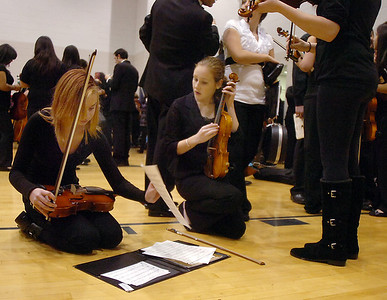 Meryl Aune, 15, left, and Rachel Ruff, 15, Legacy, prepare for their performance for the Adams 12 Five Stars Schools Orchestra Festival at Legacy High School on Saturday. For more photos please see broomfieldenterprise.com.  December 3, 2011 staff photo/ David R. Jennings