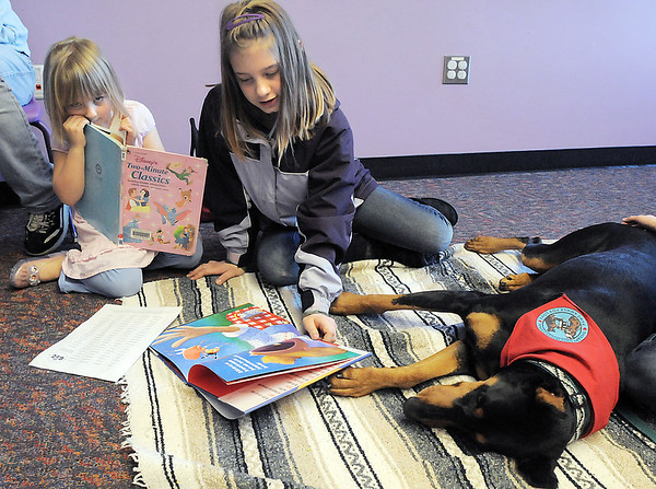 Elayna Johnson, 11, center, and her sister Eleanor, 5, left, read to Magic a 5 year old Doberman owned by Kelsey Hall during the Afternoon Read Fun program at the Children's Library of Mamie Doud Eisenhower Public Library on Thursday.<br /> <br /> January 13, 2011<br /> staff photo/David R. Jennings