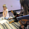 Eleanor Johnson, 5, left, reads while her sister Elayna, 11, pets Magic a 5 year old Doberman owned by Kelsey Hall during the Afternoon Read Fun program at the Children's Library of Mamie Doud Eisenhower Public Library on Thursday.<br /> <br /> January 13, 2011<br /> staff photo/David R. Jennings