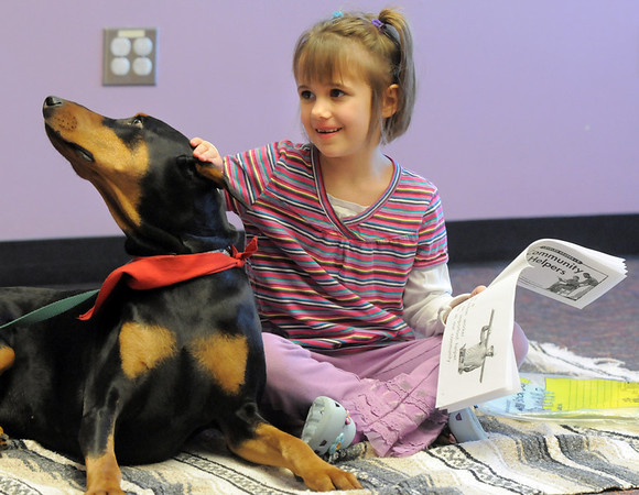 Madie Sokol, 7, pets Magic while reading to the 5 year old Doberman owned by Kelsey Hall during the Afternoon Read Fun program at the Children's Library of Mamie Doud Eisenhower Public Library on Thursday.<br /> <br /> January 13, 2011<br /> staff photo/David R. Jennings