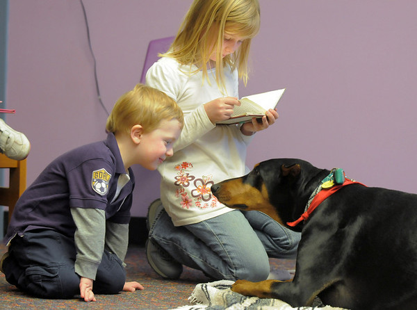 Alex Kirk, 2, left, listens while his sister Julia, 8, reads to Magic a 5 year old Doberman owned by Kelsey Hall during the Afternoon Read Fun program at the Children's Library of Mamie Doud Eisenhower Public Library on Thursday.<br /> <br /> January 13, 2011<br /> staff photo/David R. Jennings