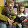 Raquel Decker with her daughter Anna, 5, pet Magic while Rebecca, 9, right,  reads to the 5 year old Doberman owned by Kelsey Hall during the Afternoon Read Fun program at the Children's Library of Mamie Doud Eisenhower Public Library on Thursday.<br /> <br /> January 13, 2011<br /> staff photo/David R. Jennings