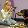 Julia Kirk, 8,  reads to Magic a 5 year old Doberman owned by Kelsey Hall during the Afternoon Read Fun program at the Children's Library of Mamie Doud Eisenhower Public Library on Thursday.<br /> <br /> January 13, 2011<br /> staff photo/David R. Jennings