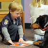 Alex Kirk, 2, shows pictures in a book to Magic a 5 year old Doberman owned by Kelsey Hall during the Afternoon Read Fun program at the Children's Library of Mamie Doud Eisenhower Public Library on Thursday.<br /> <br /> January 13, 2011<br /> staff photo/David R. Jennings