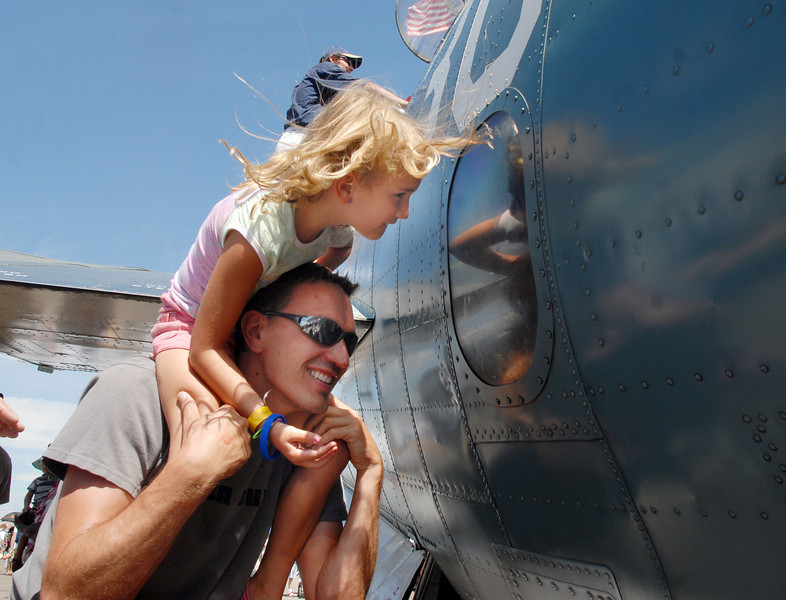 Maya Raulf, 5 1/2, and her father Chris, of Lousiville, look into a window of a WWII airplane on display during Saturday's Colorado Sport International Airshow at Rocky Mountain Metropolitan Airport.<br /> August 28, 2010<br /> staff photo/David R. Jennings