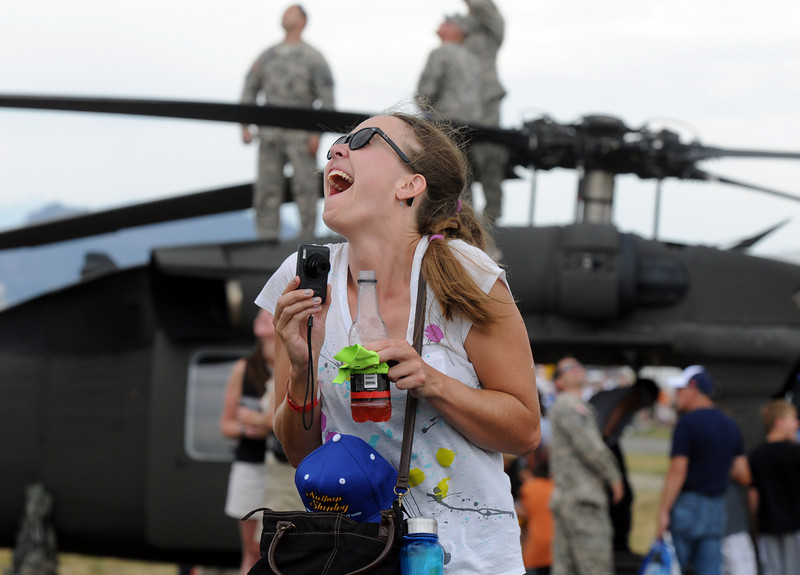 Jen Wagner, of Broomfield, reacts with excitement as an F-16 Viper flies overhead during it's performance at Saturday's Colorado Sport International Airshow at Rocky Mountain Metropolitan Airport. The airshow is in celebration of the airport's 50th anniversary.<br /> <br /> August 28, 2010<br /> staff photo/David R. Jennings