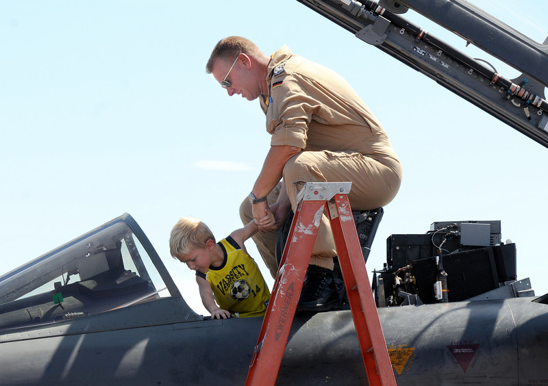 Pilot Axel Hoppe of the German Air Force helps Reed Lellbach, 5, of Westminster, into the cockpit of Hoppe's Tornado fighter during Saturday's Colorado Sport International Airshow at Rocky Mountain Metropolitan Airport.<br /> August 28, 2010<br /> staff photo/David R. Jennings