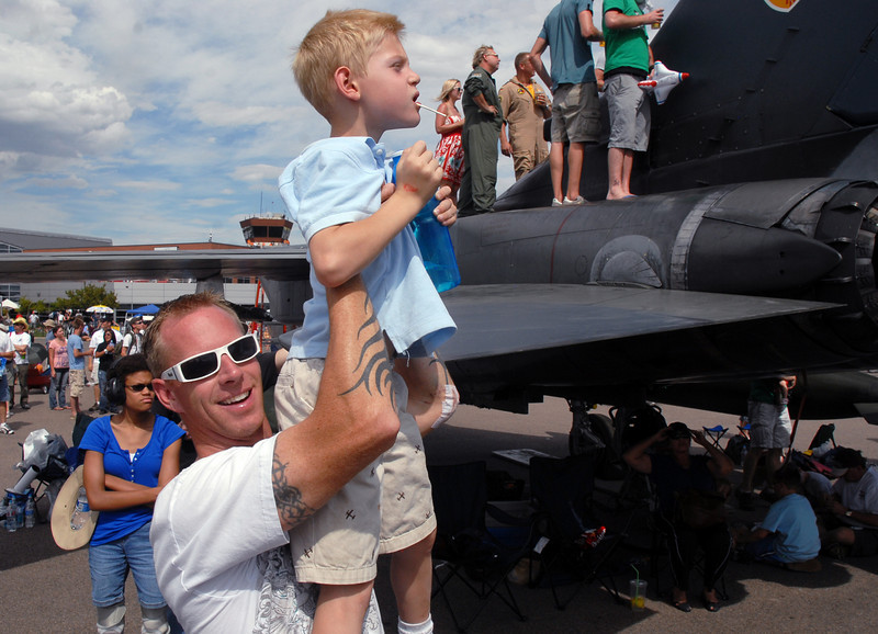 Steve Gade holds his son Dillon, 6, of Broomfeild, in the air to watch a aircraft performance during Saturday's Colorado Sport International Airshow at Rocky Mountain Metropolitan Airport.<br /> August 28, 2010<br /> staff photo/David R. Jennings