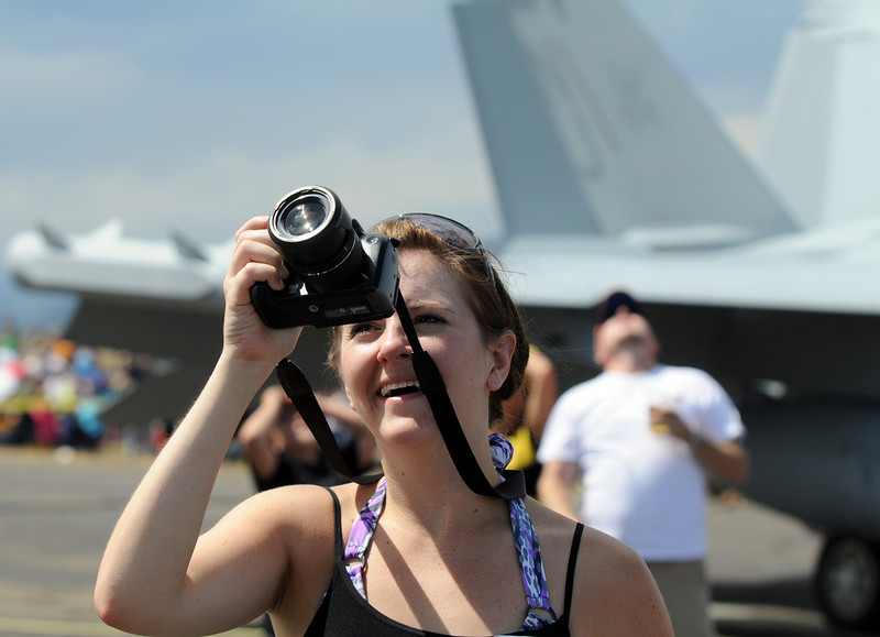Desi Lauwers, of Lakewood, takes pictures of an airplane performance during Saturday's Colorado Sport International Airshow at Rocky Mountain Metropolitan Airport.<br /> August 28, 2010<br /> staff photo/David R. Jennings