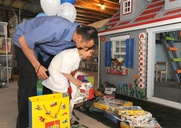 Alexander Gintchin, 6, with his father Lazar, left, look at the Lego gifts for Alexander's Lego playhouse made by volunteers from the Make-A-Wish Foundation of Colorado in the basement of thier home in the Anthem neighborhood of Broomfield on Sunday.<br /> <br /> April 29, 2012 <br /> staff photo/ David R. Jennings
