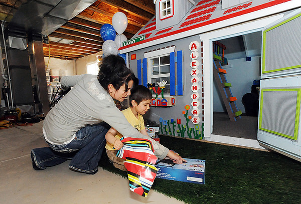 Tzvetanka Gintchin, left, shows her son Alexander, 6, a DVD player for  his Lego playhouse, made by volunteers from the Make-A-Wish Foundation of Colorado, in the basement of his home in the Anthem neighborhood of Broomfield.<br /> <br /> April 29, 2012 <br /> staff photo/ David R. Jennings