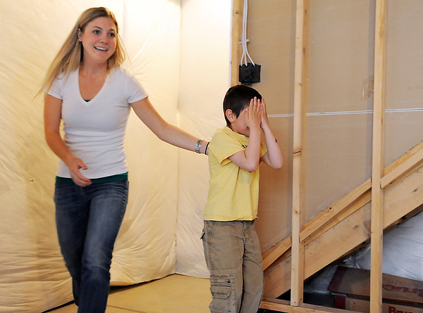 Ashlee Carey, Make-A-Wish coordinator, escorts Alexander Gintchin, 6, covering his eyes before seeing the Lego playhouse made by volunteers from the Make-A-Wish Foundation of Colorado in the basement of his home in the Anthem neighborhood of Broomfield on Sunday.<br /> <br /> April 29, 2012 <br /> staff photo/ David R. Jennings