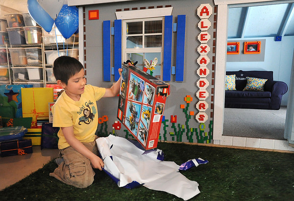 Alexander Gintchin, 6, opens gifts in front of his Lego playhouse made by volunteers from the Make-A-Wish Foundation of Colorado in the basement of his home in the Anthem neighborhood of Broomfield on Sunday.<br /> <br /> April 29, 2012 <br /> staff photo/ David R. Jennings