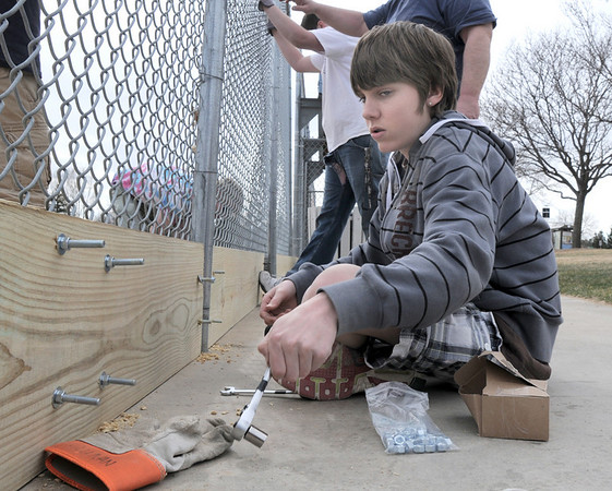 Shaney Sullivan, 13, with scout troop 767, tightens nuts on bolts  in boards for Andrew Dewey's Eagle Scout project attaching boards to the base of the fences of the David Milliman Field in Midway Park on Saturday.<br /> <br /> March 26, 2011<br /> staff photo/David R. Jennings