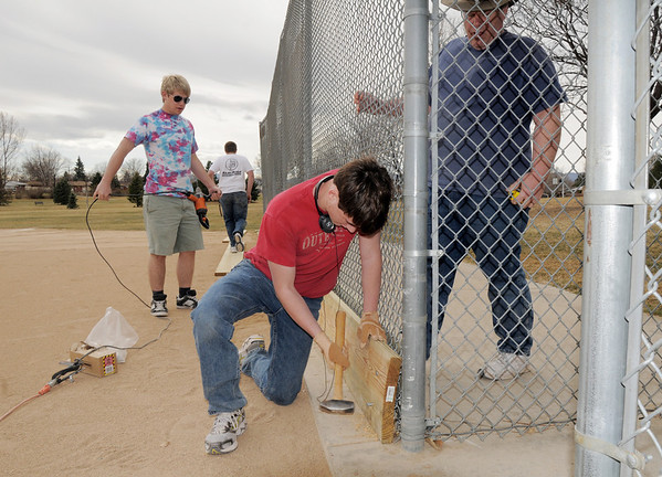 Paul Elliott, 16, center, hammers bolts through holes in base boards while Nichlas Dewey 18, left, prepares to drill holes and Matt Dewey holds the board for Andrew Dewey's Eagle Scout project puting boards on the base of the fences of the David Milliman Field in Midway Park on Saturday.<br /> <br /> March 26, 2011<br /> staff photo/David R. Jennings