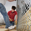 Paul Elliott, 16, hammers bolts through holes in boards while Mike Towle, 16, holds the board for Andrew Dewey's Eagle Scout project of attaching boards to the base of the fences of the David Milliman Field in Midway Park on Saturday. <br /> <br /> March 26, 2011<br /> staff photo/David R. Jennings
