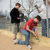 Paul Elliott, 16, hammers bolts through holes in boards while Mike Towle, 16, holds the board for the Eagle Scout project of Andrew Dewey, 15, left, which attached boards to the base of the fences of the David Milliman Field in Midway Park on Saturday. <br /> <br /> March 26, 2011<br /> staff photo/David R. Jennings