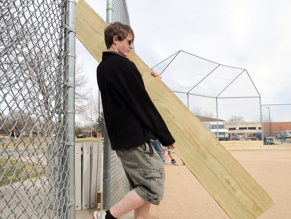 Andrew Dewey, 15, carries a board for his Eagle Scout project of attaching boards on the base of the fences of the David Milliman Field in Midway Park on Saturday.<br /> <br /> March 26, 2011<br /> staff photo/David R. Jennings