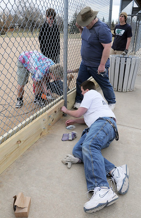 Mike Towle, 16, center, with scout troop 767, tightens bolts while Matt Dewey, right, Nicholas Dewey, 18, left, and Andrew Dewey, 16,drills hole in board for Andrew Dewey's Eagle Scout project attaching boards to the base of the fences of the David Milliman Field in Midway Park on Saturday.<br /> <br /> March 26, 2011<br /> staff photo/David R. Jennings