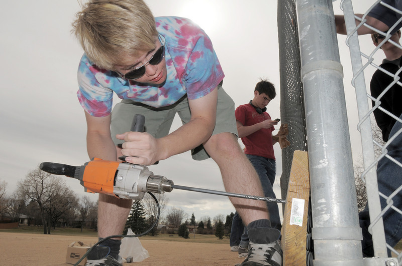 Nicholas Dewey, 18, drills holes in boards for Andrew Dewey's Eagle Scout project attaching boards to the base of the fences of the David Milliman Field in Midway Park on Saturday. Andrew Dewey, 15, with Boy Scout Troop 767, had 16 boy scouts to help with the project. the city and county's parks provided the wood and bolts. Burritos To Go provided some of the food for the scouts.<br /> <br /> March 26, 2011<br /> staff photo/David R. Jennings