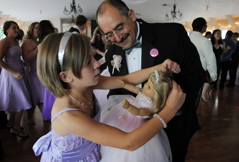 Kayla Ramirez, 10, with her father Alfonso adjusts the tiara on her doll's head which was given to her by her sister Antonia during Antonia's Quinceanera ceremony at the Miramonte Lodge.<br /> <br /> September 4, 2010<br /> staff photo/David R. Jennings