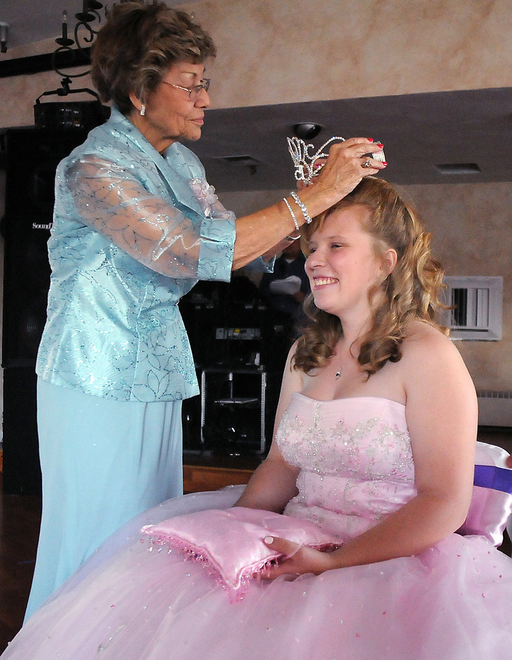 Estela Ramirez places a tiara on the head of her granddaughter Antonia Ramirez symbolizing Antonia's status of queen for the evening during the Quinceanera ceremony at the Miramonte Lodge on Saturday.<br /> <br /> September 4, 2010<br /> staff photo/David R. Jennings