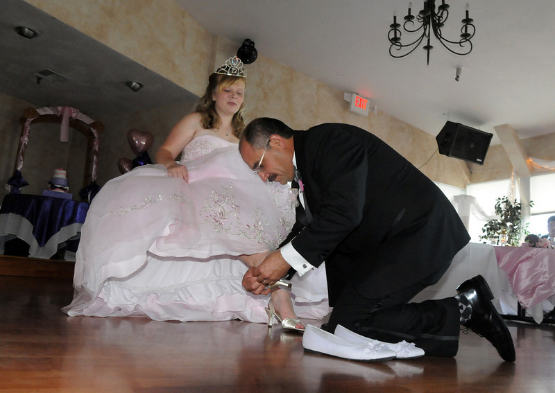 "Alfonso Ramirez changes his daughter Antonia's flat shoes for high heels to signify Antonia's ""step"" into adulthood during the Quinceanera ceremony at the Miramonte Lodge on Saturday.<br /> <br /> September 4, 2010<br /> staff photo/David R. Jennings"
