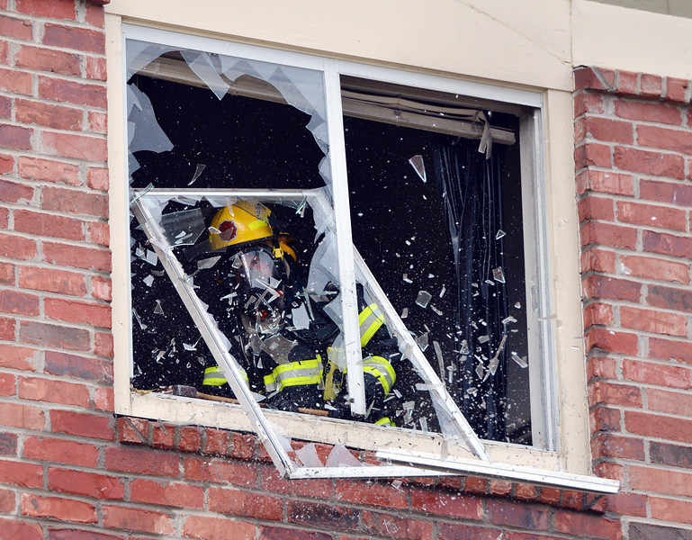 """A North Metro Fire Rescue firefighter breaks out the window of a third story apartment that was on fire at the Willow Run Village, 12601 Zuni St. on Wednesday.<br /> <br /> June27, 2012<br /> staff photo/ David R. Jennings<br /> <br /> for more photos and video please go to  <a href=""""http://www.broomfieldenterprise.com"""">http://www.broomfieldenterprise.com</a>"""