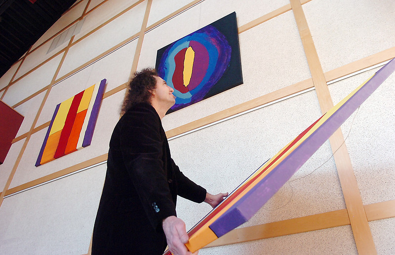 Broomfield artist Arlo White holds a painting for his show, Planet Rock, in the lobby of the Broomfield Auditorium on Friday.<br /> <br /> January 6, 2012<br /> staff photo/ David R. Jennings