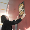 Broomfield artist Arlo White hangs a painting on the wall with his wife Kim, left, for his Planet Rock art show in the lobby of the Broomfield Auditorium on Friday.<br /> <br /> January 6, 2012<br /> staff photo/ David R. Jennings