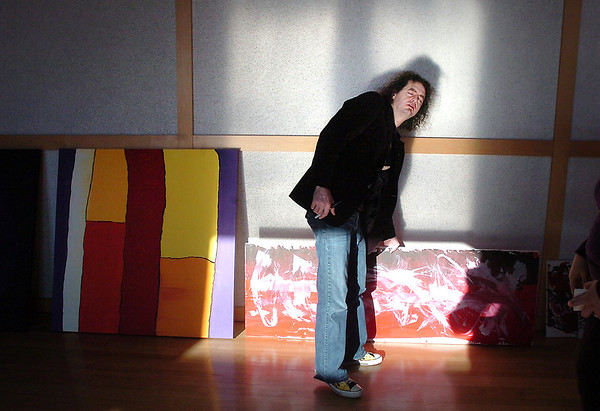 Broomfield artist Arlo White looks for the correct wall for a painitng while hanging his show, Planet Rock, in the lobby of the Broomfield Auditorium on Friday.<br /> <br /> January 6, 2012<br /> staff photo/ David R. Jennings