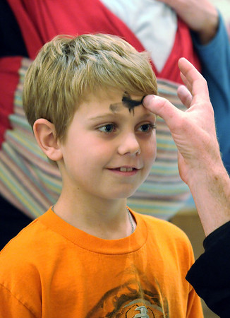 Eddie Hartnett, 7, receives ashes from Pastor Scott McAnally during the Lutheran Church of Hope children's Ash Wednesday service.<br /> <br /> February 17, 2010<br /> Staff photo/David R. Jennings