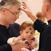 Steve Roth and his daughter Nora, 18 months old,  receives ashes from Pastor Scott McAnally during the Lutheran Church of Hope children's Ash Wednesday service.<br /> <br /> February 17, 2010<br /> Staff photo/David R. Jennings