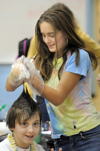 Aric Silver, 9, has his hair done at the crazy hair booth by Audrey Faulkenburg, 14,  during the Aspen Creek K-8 Fall Festival on Friday. <br /> November 5, 2010<br /> staff photo/David R. Jennings