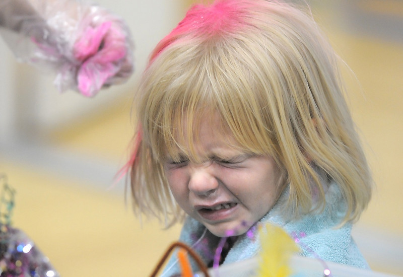 Avery Gilbert, 4, closes her eyes while her hair is sprayed pink at the crazy hair booth during the Aspen Creek K-8 Fall Festival on Friday. <br /> November 5, 2010<br /> staff photo/David R. Jennings