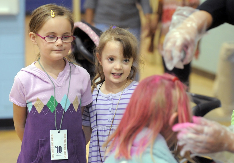 Friends Abby Baker, 6, left, and Sophia Mechling, 6, watch a girl having her hair done in the crazy hair booth during the Aspen Creek K-8 Fall Festival on Friday. <br /> November 5, 2010<br /> staff photo/David R. Jennings