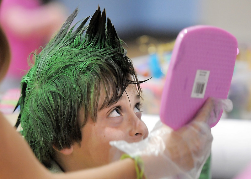 Aric Silver, 9, looks at his hair in the mirror held by Audrey Faulkenburg, 14, during the Aspen Creek K-8 Fall Festival on Friday. <br /> November 5, 2010<br /> staff photo/David R. Jennings