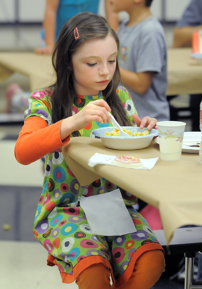 Sydney Ayers, 8, carefully eats her mac and cheese dinner made by the Broomfield High Pro Start students during the Aspen Creek K-8 Fall Festival on Friday. <br /> November 5, 2010<br /> staff photo/David R. Jennings