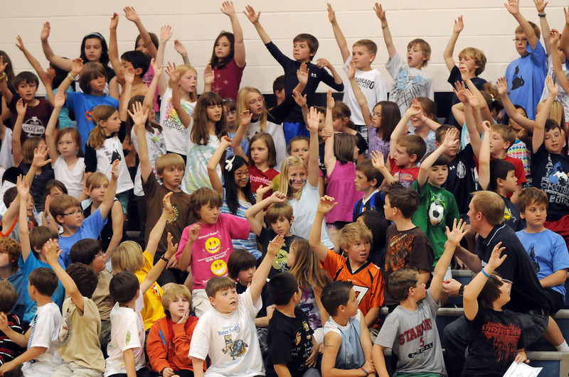 Aspen Creek student's raise their hands to be chosen to compete in a dance game during the school's 10th anniversary celebration assembly on Friday.<br /> May 21, 2010<br /> Staff photo/ David R. Jennings