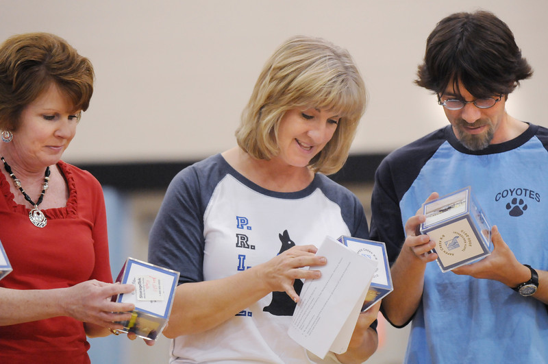 Aspen Creek teachers Jean Witt, left, kindergarten, with 4th grade teachers Heidi Dery and Brian Geraghty look at pictures of themselves  from 10 years ago on picture cubes during the school's 10th anniversary celebration assembly on Friday.<br /> May 21, 2010<br /> Staff photo/ David R. Jennings