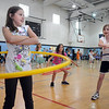 Third graders Erika Fedynyshyn, left, and Gretta Barrington test their skills at the hula hoop for a contest during Aspen Creek's 10th anniversary celebration assembly on Friday.<br /> May 21, 2010<br /> Staff photo/ David R. Jennings