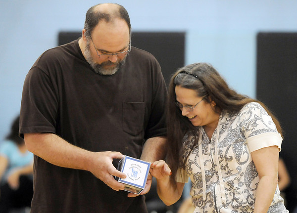 Aspen Creek head custodian LaVern Schafer, left, and custodian Janet Reetz look at pictures of Schafer from 10 years ago on his gift of a picture cube during the school's 10th anniversary celebration assembly on Friday.<br /> May 21, 2010<br /> Staff photo/ David R. Jennings