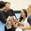 Aspen Creek staff members 4th grade teacher Brian Geraghty, left, head custodian LaVern Schafer, custodian Janet Reetz and 4th grade teacher Heidi Dery share their picture cubes with pictures of themselves from 10 years ago during the school's 10th anniversary celebration assembly on Friday.<br /> May 21, 2010<br /> Staff photo/ David R. Jennings