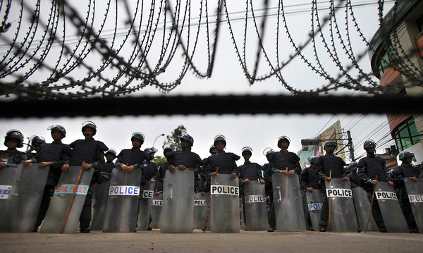 Nepalese policemen in riot gear stand guard near a barricade in Katmandu, Nepal, Sunday, May 2, 2010. Thousands of Maoist supporters armed with bamboo sticks marched through the city streets in Nepal Sunday to enforce an indefinite general strike called by them to demand Prime Minister Madhav Kumar Nepal's resignation. (AP Photo/Altaf Qadri)